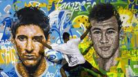 Lionel Messi dan Neymar menjadi pujaan publik sepakbola dunia. Mural ini terdapat di Rio de Janeiro, Brasil. (AFP Photo/Yasuyoshi Chiba)
