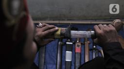 Iwan menunjukkan sejumlah senjata yang biasa digunakan dalam latihan. Sudah 5 tahun pria yang sehari-hari berprofesi sebagai pegawai toko itu membuka Perguruan Pencak Silat Chingkrik Betawi Rusunawa meskipun dengan keterbatasan tempat latihan. (merdeka.com/Iqbal S Nugroho)