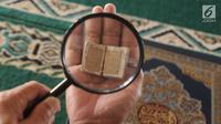 Kyai Tubagus Muhammad Tamyiz membaca Alquran mini bertinta emas dengan bantuan kaca pembesar di Masjid Jami Darusalam, Sukaraja, Bogor, Jawa Barat, Kamis (24/5). Alquran mini tersebut berukuran 10 mm x 10 mm. (Merdeka.com/Arie Basuki)