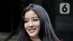 Pramugari Garuda Indonesia, Siwi Widi tersenyum usai diperiksa penyidik di Gedung Ditreskrimsus Polda Metro Jaya, Jakarta, Senin (20/1/2020). Siwi diperiksa sebagai pelapor kasus pencemaran nama baik oleh akun Twitter @digeembok. (merdeka.com/Iqbal S. Nugroho)