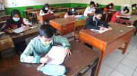 Murid kelas V mengikuti ujian Penilaian Akhir Semester (PAS) tahun pelajaran 2020/2021 di Madrasah Ibtidayah (MI) Assu'ada di Pancoran Mas, Depok, Jawa Barat, Selasa (1/12/2020). Ujian dilaksanakan dengan menerapkan protokol kesehatan dalam kelas. (merdeka.com/Arie Basuki)