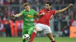 Pemain Bayern Munchen, Javi Martinez (kanan), berebut bola dengan pemain Borussia Monchengladbach, Andre Hahn, dalam laga pekan ke-8 Bundesliga 2016-2017, Sabtu (23/10/2016). (AFP/Christof Stache)