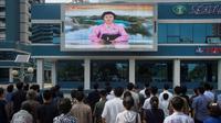 Warga menonton sebuah layar video besar di Mirae Scientists Street di Pyongyang yang menampilkan pembaca berita Ri Chun-Hee saat dia mengumumkan bahwa negara tersebut telah berhasil menguji sebuah bom hidrogen pada Senin (3/9). (AFP Photo/Kim Won-Jin)