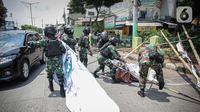 Anggota TNI mencopot paksa baliho Rizieq Shihab yang terpasang di sekitar kawasan Petamburan, Jakarta, Jumat (20/11/2020). Pencopotan dilakukan karena menyalahi aturan yang telah ditetapkan. (Liputan6.com/Faizal Fanani)