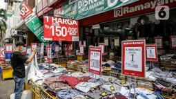 Pengunjung melihat pakaian yang dijajakan di salah satu tenant di Pasar Baru, Jakarta, Rabu (5/4/2021). Memasuki minggu terakhir bulan Ramadhan 2021, Pasar Baru tampak sepi pengunjung. (Liputan6.com/Faizal Fanani)