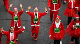 Peserta berkostum Sinterklas melambaikan tangan saat mengikuti Santa Claus Run di Madrid, Spanyol, Minggu (9/12). Ribuan orang berjalan dan berlari dalam perlombaan Santa tahunan melintasi jalan-jalan ibu kota Spanyol. (Gabriel BOUYS / AFP)