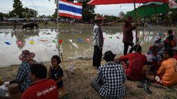 Penduduk setempat menunggu dimulainya pada festival lomba balap kerbau di Chonburi, Minggu (16/7). Festival tahunan di Thailand ini merupakan tradisi untuk menyambut datangnya musim panen padi. (LILLIAN SUWANRUMPHA / AFP)