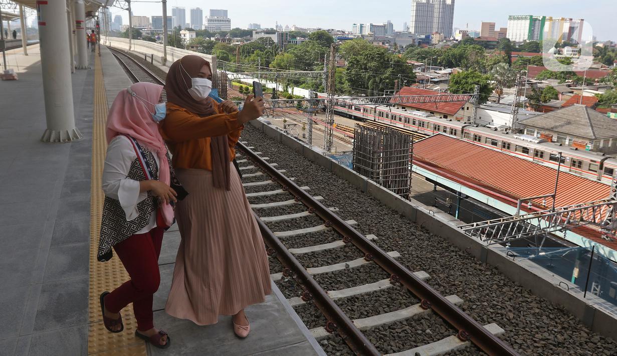 Penumpang berswafoto sambil menunggu kedatangan KRL Commuter Line di Stasiun Manggarai, Jakarta, Minggu (26/9/2021). Jalur layang (elevated track) KRL Bogor Line di Stasiun Manggarai yang terdiri dari empat peron bagi penumpang kereta relasi tujuan Jakarta-Bogor. (Liputan6.com/Herman Zakharia)