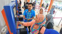 Petugas membantu calon penumpang melakukan transaksi di mesin penjual tiket di Stasiun Senen, Jakarta, Selasa (20/12). Jelang libur Natal dan tahun baru tiket Kereta Api sudah habis untuk keberangkatan Jateng dan Jatim. (Liputan6.com/Angga Yuniar)