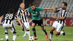 Pemain Schalke 04 Marco Hoger dihadang pemain PAOK pada Putar Liga Champions kedua pertandingan sepak bola di Stadion Toumpa di Thessaloniki (27/08/2013).(AFP/Sakis Mitrolidis).