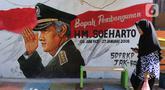 Seorang warga melintasi mural di Kampung Budaya Kawasan Jakarta Barat, Selasa (19/11/2019). Pemprov Jakarta Barat melakukan penataan kawasan pemukiman di beberapa lokasi, salah satunya di Jalan Katalia I Timur. (Liputan6.com/Herman Zakharia)