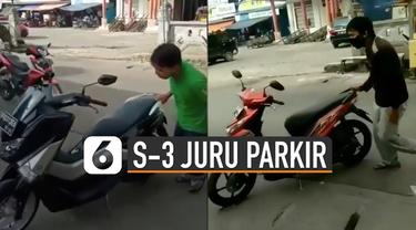 Seorang pria unjuk keahlian memarkirkan sepeda motor dengan satu tangan.