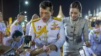 Raja Maha Vajiralongkorn dan Ratu Suthida menyapa pendukungnya di Bangkok, Thailand, Minggu (1/11/2020). Di bawah tekanan yang meningkat dari pengunjuk rasa yang menuntut reformasi pada monarki, Raja dan Ratu Thailand bertemu dengan ribuan pendukung yang memujanya. (AP Photo/Wason Wanichakorn)