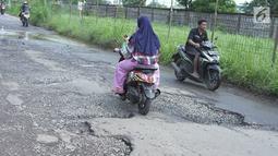 Pengendara sepeda motor melintasi jalan yang rusak di Jalan Raya Gas Alam, Depok, Jawa Barat, Selasa (7/5). Kondisi jalan yang tidak kunjung diperbaiki tersebut menjadi kubangan air setiap hujan serta berbahaya bagi keselamatan pengguna jalan. (Liputan6.com/Immanuel Antonius)