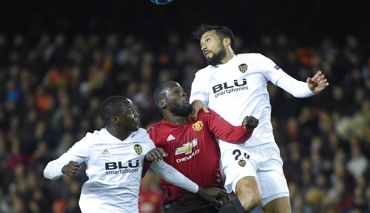 Romelu Lukaku berduel dengan bek Valencia, Ezequiel Garay pada laga terakhir grup H Liga Champions yang berlangsung di stadion Mestalla, Valencia, Rabu (13/12). Manchester United kalah 1-2 atas Valencia. (AFP/Jose Jordan)