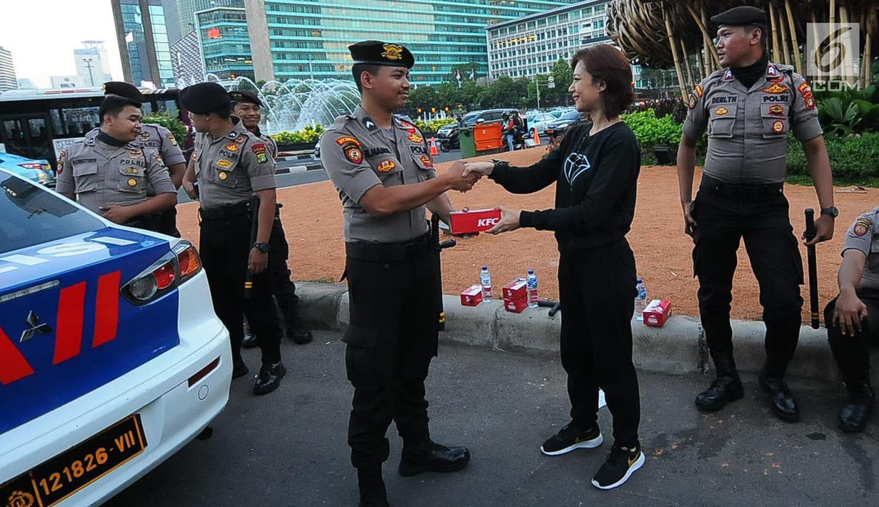 Relawan TKN Jokowi-Ma'ruf Amin membagikan makanan berbuka puasa kepada aparat kepolisian yang melakukan penjagaan di kawasan Bundaran HI, Jakarta, Jumat (24/5/2019). Kegiatan ini sebagai bentuk kepedulian untuk aparat yang telah menjaga keamanan di Jakarta. (Liputan6.com/Angga Yuniar)