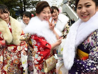Sejumlah gadis di Jepang berkimono menuju salah satu taman hiburan di Tokyo, Jepang, Senin (9/1). Kehadiran mereka untuk merayakan Coming of Age Day atau Hari Datangnya Kedewasaan. (AFP Photo/ TORU YAMANAKA)