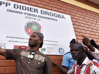 Bintang sepak bola asal Pantai Gading, Didier Drogba melakukan foto selfie saat membuka sekolah di Onahio, Pokou-Kouamekro, Pantai Gading, (20/1/2018).  Drogba menjadi salah satu sponsor utama untuk sekolah tersebut. (AFP/Sia Kambou)