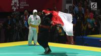 Pesilat Indonesia Pipiet Kamelia berselebrasi membawa bendera Merah Putih usai mengalahkan Thi Cam Nhi Nguyen dari Vietnam pada final nomor 60-65 kg putri pencak silat Asian Games 2018, Jakarta, Rabu (29/8). (Merdeka.com/Imam Buhori)