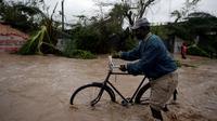 Seorang warga menuntun sepedanya saat melintasi banjir yang disebabkan oleh hantam Badai Matthew di Haiti (4/10). Keganasan Badai Matthew ini telah meluluhlantakkan wilayah Haiti. (REUTERS/Andres Martinez Casares)