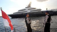 Petugas Polda Bali bersenjata laras panjang melakukan penjagaan saat kapal pesiar mewah (yacht) Equanimity terlihat berada di pelabuhan Benoa, Rabu (28/2). Equanimity juga disebut-sebut sebagai yacht terbesar ke-54 di dunia. (AP/Ambros Boli Berani)