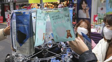 Dua wanita membeli masker wajah di sebuah toko di Seoul, Korea Selatan (28/1/2020). Penyebaran wabah virus corona berimbas pada peningkatan penjualan masker pelindung, sehingga bisnis ini berkembang pesat di Asia. (AP Photo/Ahn Young-joon)