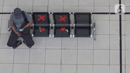 Calon penumpang melihat ponsel sambil menanti waktu keberangkatan bus Antar Kota Antar Provinsi di Terminal Bus Terpadu Pulo Gebang, Jakarta, Kamis (31/12/2020). Memasuki libur pergantian tahun sejumlah calon penumpang terus berdatangan di Terminal Bus Terpadu Pulo Gebang. (Liputan6.com/Helmi Fithri