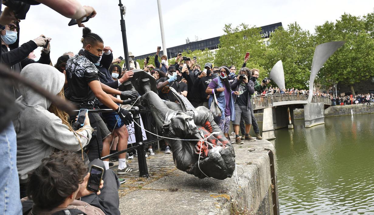 Demonstran melempar patung pedagang budak Edward Colston ke Pelabuhan Bristol saat protes Black Lives Matter di Bristol, Inggris, Minggu (7/6/2020). Aksi tersebut dilakukan sebagai bentuk protes atas kematian George Floyd saat ditangkap oleh polisi di Amerika Serikat. (Ben Birchall/PA via AP)