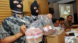 Dua penyidik KPK memperlihatkan uang pecahan Rp100 ribu dalam rilis Operasi Tangkap Tangan (OTT) Ketua DPRD Bangkalan Fuad Amin Imron di Gedung KPK, Jakarta, Selasa (2/12/2014). (Liputan6.com/Miftahul Hayat)