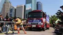 Petugas pemadam kebakaran Lim Sung-joo menarik sebuah truk pemadam kebakaran dengan seutas tali saat Safe Seoul Festival di Seoul, Korea Selatan, Kamis (9/5/2019). Festival ini mengampanyekan kesadaran keselamatan atas kebakaran, bencana alam hingga berlalu lintas. (AP Photo/Ahn Young-joon)