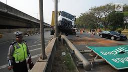 Petugas polisi berada di lokasi kecelakaan kendaraan berat kontainer yang menabrak jalur pembatas pintu masuk tol akses Tanjung Priok di Jalan Raya Cilincing, Jakarta Utara, Sabtu (17/8/2019). (merdeka.com/Arie Basuki)