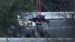 Crane mengevakuasi bangkai helikopter dari lokasi kecelakaan yang menewaskan pemilik Leicester City Vichai Srivaddhanaprabha di Leicester, Inggris, Kamis (1/11). Selain Vichai, 4 orang lainnya juga tewas dalam kecelakaan tersebut. (Aaron Chown/PA via AP)