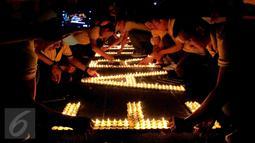 Puluhan karyawan Artha Graha Peduli menyalakan lilin saat menggelar Earth Hours di kawasan SCBD Jakarta, Sabtu (25/3). Kegiatan ini mendukung kampanye perubahan iklim dan pencegahan pemanasan global dengan pemadaman listrik. (Liputan6.com/Fery Pradolo)