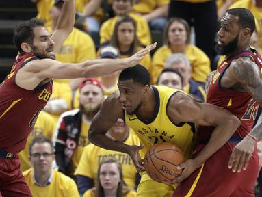 Pemain Indiana Pacers, Thaddeus Young (tengah) mencoba melewati adangan pemain Cleveland Cavaliers pada game keenam playoffs NBA basketball di Bankers Life Fieldhouse, Indianapolis, (27/4/2018). Pacers menang 121-87. (AP/Darron Cummings)