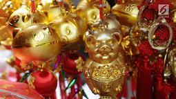 Gantungan kunci bertema Imlek dijual di kawasan Glodok, Jakarta, Kamis (31/1). Pernak-pernik Imlek bershio babi tanah sudah mulai ramai dijual. (Liputan6.com/Herman Zakharia)