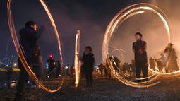 Warga Korea Selatan membuat lingkaran api selama perayaan  Bulan Purnama pertama tahun baru Imlek di Seoul (17/2). Permainan ini dipercaya dapat menyuburkan tanah dan menyingkirkannya hama sehingga memastikan hasil panen melimpah. (AFP Photo/Jung Yeon-je)