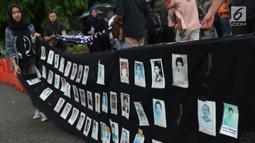 Aktivis bersiap menggulung deretan foto korban saat aksi Kamisan ke-562 di depan Istana Merdeka, Jakarta, Kamis (15/11). Mereka meminta pemerintah menyelesaikan kasus pelanggaran HAM berat khususnya Tragedi Semanggi 1. (Liputan6.com/Helmi Fithriansyah)