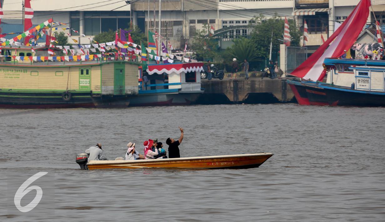 Warga berselfi diatas sampan untuk menyeberang di sungai Kapuas, Pontianak, Kalimantan Barat, Sabtu (22/8/2015). Perahu Sampan sampai saat ini masih diminati warga sebagai pilihan moda transportasi sederhana di Sungai Kapuas. (Liputan6.com/Faizal Fanani)
