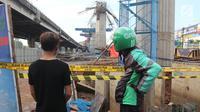 Pengemudi ojek online mengamati kondisi tiang girder Tol Bekasi-Cawang-Kampung Melayu (Becakayu) yang ambruk di Kebon Nanas, Jakarta Timur, Selasa (20/2). Tak ada penutupan jalur akibat robohnya tiang pancang tol Becakayu. (Liputan6.com/Arya Manggala)