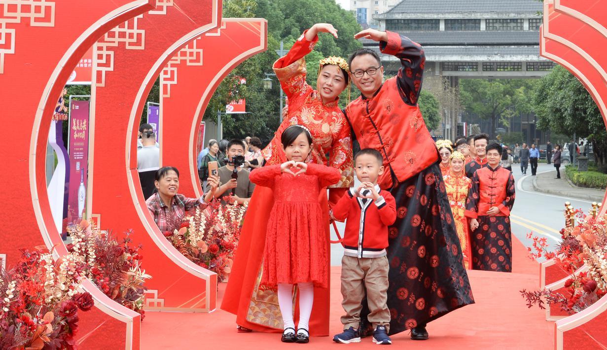 Sepasang mempelai berpose dengan para pengiring pengantin dalam pernikahan massal bergaya China di Changsha, Provinsi Hunan, China, 25 September 2020. Sebanyak 71 pasangan resmi menjadi suami-istri usai mengikuti upacara pernikahan tradisional dalam acara nikah massal. (Xinhua/Chen Zhenhai)