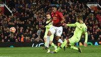 Bek Barcelona, Gerard Pique memblok tendangan bola pemain depan Manchester United, Anthony Martial pada leg pertama perempat final Liga Champions di Stadion Old Trafford, Rabu (10/4). Barcelona menang tipis 1-0 atas Manchester United. (Oli SCARFF / AFP)