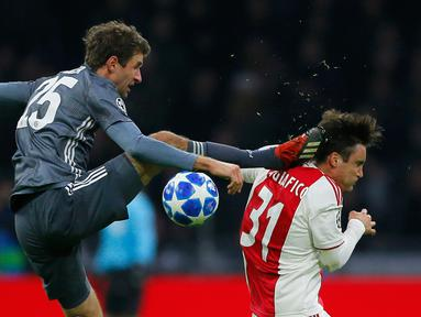 Gelandang Bayern Munchen Thomas Mueller (kiri) menendang kepala bek Ajax Amsterdam Nicolas Tagliafico dalam laga Grup E Liga Champions di Amsterdam, Belanda, Rabu (12/12). Mueller menendang Tagliafico dengan kaki kanannya. (AP Photo/Peter Dejong)