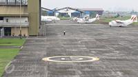 Petugas mengamati pesawat terbang yang terparkir di Bandara Pondok Cabe di Pamulang, Tangsel, Senin (22/2). Maret mendatang, maskapai Garuda Indonesia akan membuka penerbangan dari bandara milik PT Pertamina (persero) ini. (Liputan6.com/Immanuel Antonius)