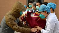 Pasien yang dinyatakan sembuh dari virus corona memberi salam perpisahan kepada petugas medis di Rumah Sakit Afiliasi Pertama Universitas Zhengzhou, Provinsi Henan, China, Selasa (4/2/2020). Ini adalah pasien pertama yang dinyatakan sembuh dari virus corona di Shaanxi. (Xinhua/Liu Xiao)