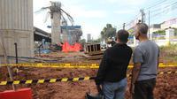 Dua orang warga melihat kondisi tiang girder Tol Bekasi-Cawang-Kampung Melayu (Becakayu) yang ambruk di Kebon Nanas, Jakarta Timur, Selasa (20/2). Tak ada penutupan jalur akibat robohnya tiang pancang tol Becakayu. (Liputan6.com/Arya Manggala)