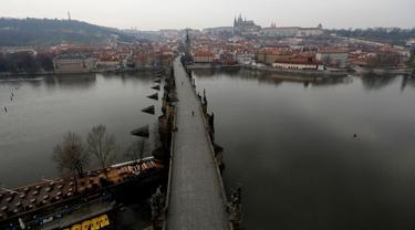 Pemandangan Jembatan Charles yang hampir kosong di Praha, Republik Ceko, Jumat, (20/3/2020). Pemerintah Republik Ceko telah menyetujui langkah dramatis lebih lanjut untuk mencoba dan membendung penyebaran virus corona baru yang disebut COVID-19. (AP Photo/Petr David Josek)