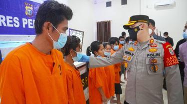 Kepala Polres Pelalawan AKBP Indra Wijatmiko berbincang dengan seorang tersangka penganiayaan sadis yang menuduh korbannya sebagai dukun santet.