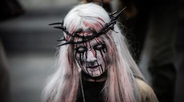 Penggemar film horor memakai kostum dan berdandan menyerupai zombie saat berpartisipasi dalam acara Zombie Walk di Place de la Republique, Paris, Sabtu (12/10/2019). Sejak 2008, acara Zombie Walk digelar untuk orang-orang yang terobsesi dengan mayat hidup. (Martin BUREAU / AFP)