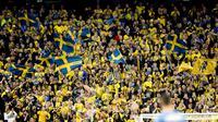 Pendukung timnas Swedia mengibarkan bendera dan meneriakan yel-yel saat menyaksikan pertandingan antara Swedia menjamu Italia dalam kualifikasi Piala Dunia 2018 di Solna, Swedia (10/11). Swedia menang 1-0 atas Italia. (AP Photo/Frank Augstein)