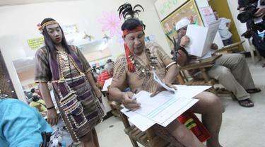 Kepala suku Igorot, Nicolas Cawed dibantu putrinya Mia Nicole mengisi kertas suara dalam pemilihan presiden di sebuah TPS di Baguio City, Manila Utara, Senin (9/5). Sekitar 50 juta warga Filipina mengikuti pemilihan Presiden. (AFP PHOTO/JJ LANDINGIN)